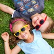 Picture presenting kids relaxinng on the grass — Foto Stock