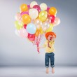 Small jumping boy holding bunch of balloons — Stock Photo