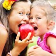 Joyful cute kids sharing an apple — Stock fotografie