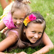 Two smiling girls playing on the summer grass — Stock Photo