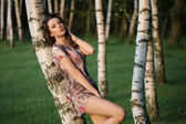 Alluring adult girl leaning on the birch — Stock Photo