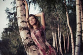 An attractive girl leaning on the birch — Stock Photo