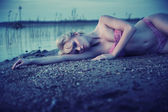 Tired blonde girl lying on the beach — Stock Photo