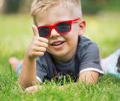 портрет счастливым мальчиком, показывает палец вверх жест — Стоковое фото