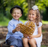 Two laughing kids holding wicker heart — 图库照片