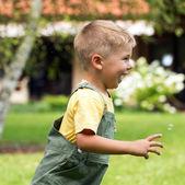 Cute small boy chasing soap bubbles — Stock Photo