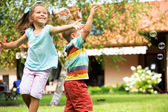 Cheerful kids chasing the soap bubbles — Stock Photo