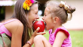 Sweet red apple being bitten by sisters — Stock Photo