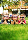 Trio kids showing their tongues — Stock Photo