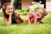 Young sisters playing together in their garden — Stock Photo