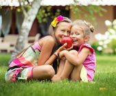 Cute sisters posing with huge red apple — Stock Photo