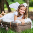 Small cute angel resting on the suitcase — Stock Photo