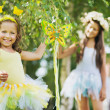 Two smiling cute sisters at the garden — Stock Photo