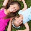 Cute girls lying on the grass — Stock Photo