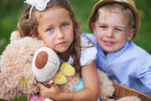 Glad kids holding cute teddy bear — Stock Photo
