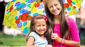 Young sisters posing with colorful umbrella — Stock Photo