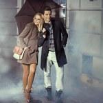 Cute couple with huge umbrella — Stock Photo