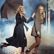 Two blonde ladies running during rain — Stock Photo