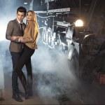 Elegant couple at the railway station — Stock Photo