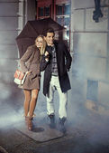 Cute couple with huge umbrella — Stock Photo
