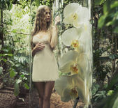 Blonde woman with curly hair among greenery — Стоковое фото
