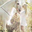 Blonde beautiful woman touching mejestic horse — 图库照片