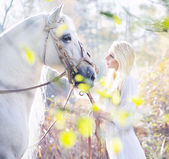 Blonde nymph with the white horse — Stockfoto