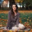 Beautiful woman relaxing in autumn park — Stock Photo