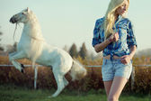 Alluring blonde beauty with majestic horse — Stock Photo