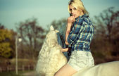 Mystery blonde woman riding a horse — Stock Photo