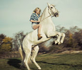 Serious blonde woman riding the horse — Stockfoto