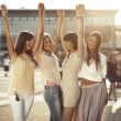 Four girlfriends in the victorious gesture — Stock Photo