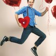 Laughing and jumping man with valentine's balloons — Stock Photo #39020497