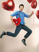 Laughing and jumping man with valentine's balloons — Stock Photo