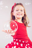 Little girl making large soap bubbles — Stock Photo