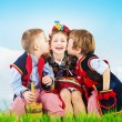 Foto Stock: Three cheerful kids wearing national costumes