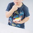 Stock Photo: Small boy tasting fruit cake