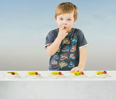 Cute little boy with delicious fruit cake — Stockfoto
