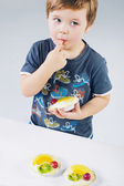 Small boy tasting the fruit cake — Stock Photo