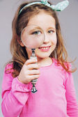 Beautiful little girl looking through a magnifying glass — Stock Photo