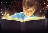 Amazed young boy with magic book — Stock Photo