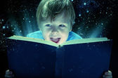 Laughing small boy with the magic book — Stock Photo