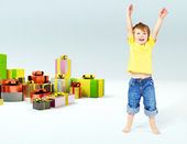Cute little boy with lots of gifts — Stock Photo
