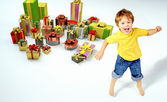 Amazed little boy with lots of presents — Stockfoto