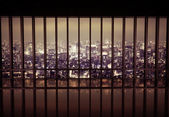 Night city behind the grating — Stock Photo