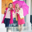 Attractive girlfriends with the colorful umbrellas — Stock Photo