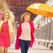 Self-confident girls walking with umbrellas — Stock Photo