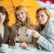 Three women, the coffee and the umbrella — Stock Photo