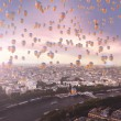 Lots of flying balloons with the city in the background — Stok fotoğraf