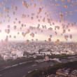 Lots of flying balloons with the city in the background — Stock fotografie
